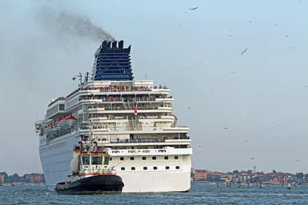 accurately: Powerful tugboat while accurately manoeuvre the large cruise ship out of the port city Stock Photo