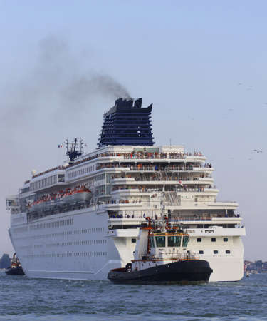 manoeuvre: Powerful tugboat while accurately manoeuvre the large cruise ship out of the port city Stock Photo