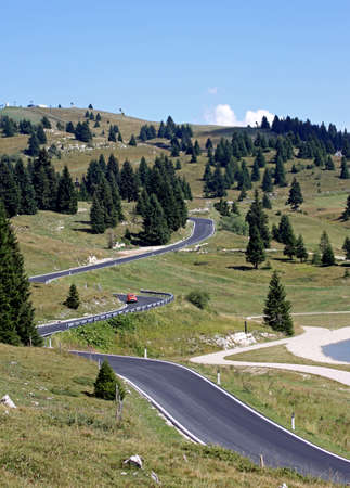 tortuous: ong and winding road full of bends in the mountain meadows Stock Photo