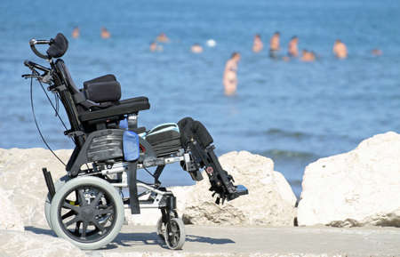 new wheelchair for disabled people on the Jetty of rocks by the sea in summer photo