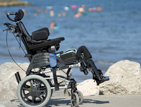 new wheelchair for disabled people on the Jetty of rocks by the sea