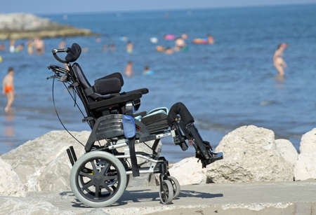 new wheelchair for disabled people on the Jetty of rocks by the sea in summer 3 Stock Photo
