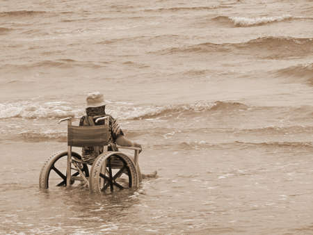elderly woman in a wheelchair in the sea with old sepia color photo