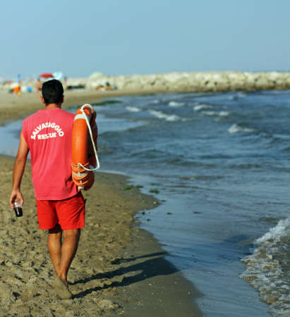 recanati: Lifeguard on the beach with a glass of soda and orange lifesaver Stock Photo