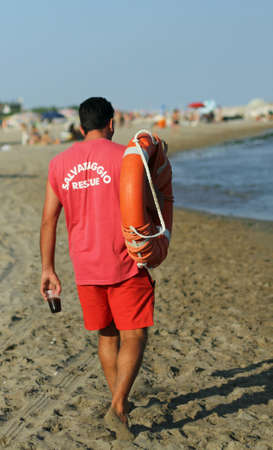 recanati: Lifeguard on the beach with a glass of soda and lifesaver Stock Photo