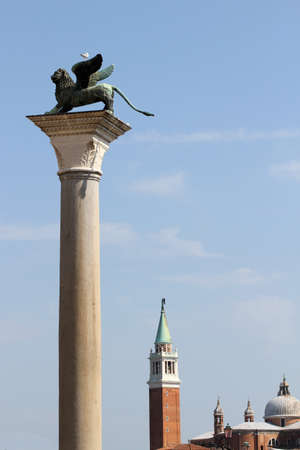 procuratie: beautiful golden statue of winged Lion, symbol of the serenissima Republic of Venice in Northern Italy and bell tower of San giorgio Church Stock Photo