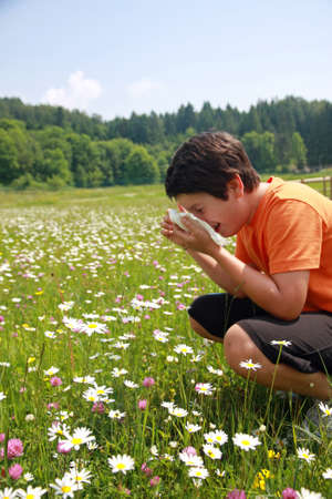 child with an allergy to pollen while sneeze in the middle of the flowers