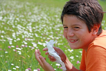 mite: child with an allergy to pollen while sneeze in the middle of the flowers