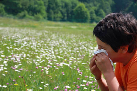 with pollen: child with an allergy to pollen while you blow your nose with a white handkerchief