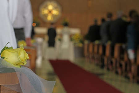 Christian Church during the rite of marriage with a yellow rose and the bride and groom photo