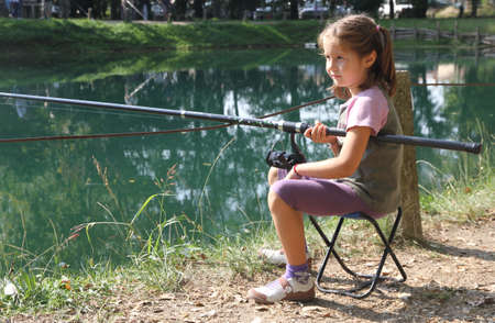 pretty little girl with the fishing rod on the shores of lake fishing 2 photo
