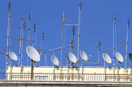 electromagnetism: series of TV antennas and satellite dishes to receive television and radio programs over the roof of the big house Stock Photo