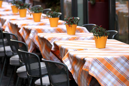 typical tables laid with checkered tablecloth for a stylish Italian restaurant photo