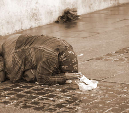 marginalized: ancient Gypsy with lurid clothes while begging on the street