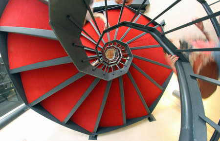 spiral staircase with red carpet for a dizzying ascent toward the offices Stock Photo