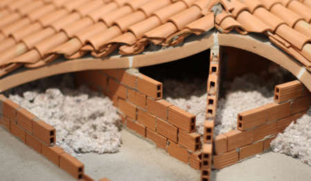 save heating costs: Attic insulation with the insulating material of the House made of terracotta brick red Stock Photo