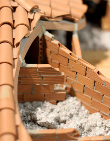insulate: Attic insulation with the insulating material of the House made of terracotta red brick Stock Photo