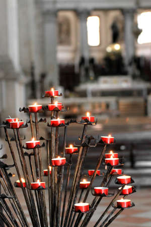 Red candles by the faithful inside a church during the Holy Mass photo