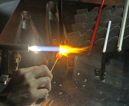 glazier: Glazier with gas torch lit while blending glass