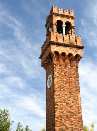 high Bell Tower with clock in the island of Murano near Venice photo