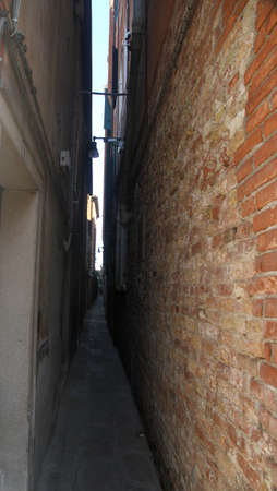 both sides: very narrow calle of Venice with the high houses on both sides of the street