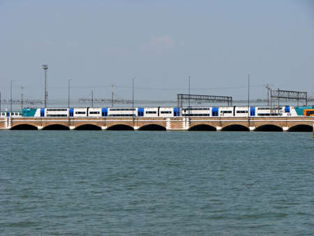 the mainland: trains  over the ponte della libertà that connects the island of Venice to the Mainland and the city of Mestre Stock Photo