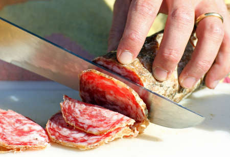 causes: salami sliced by butchers hands in the shop