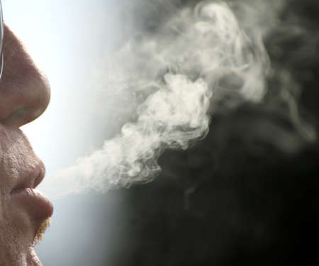 snort: backlit cigarette smoke and chain-smoker in a moment of relaxation