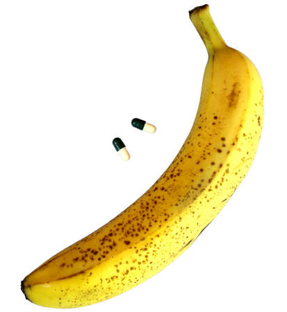 cavernosum: big yellow banana with two pills for male issues Stock Photo