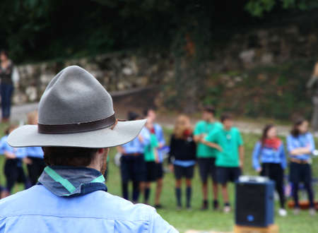 Chief scout with the typical large Hat while controlling their kids to camp Stock Photo