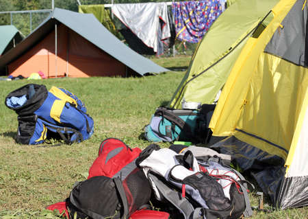 midst: many backpacks of hikers in the midst of camping tents