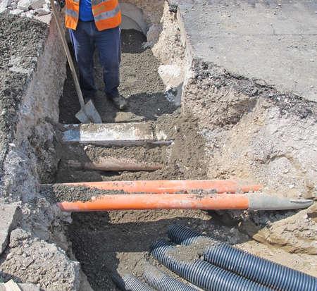 waterleiding: leggen van glasvezel en elektrische kabels in een wegwerkzaamheden en een werknemer 2