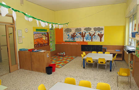 classroom in a kindergarten with tables and little yellow chairs