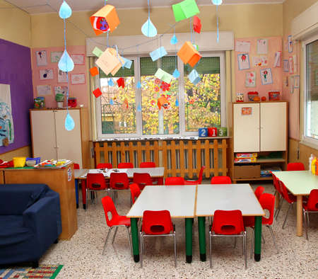 classroom in a kindergarten with tables and little red chairs