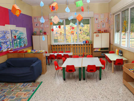 decorated classroom in a kindergarten with tables and little red chairs