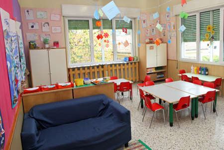 classroom in a kindergarten with tables and little chairs and blue sofa