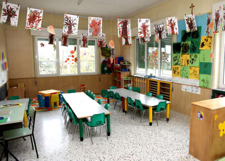 in a class of a nursery with drawings of children hanging photo