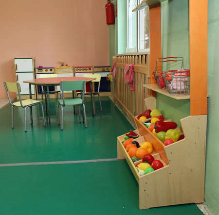 Salon of a nursery with stand of fruit and wooden kitchen toy photo