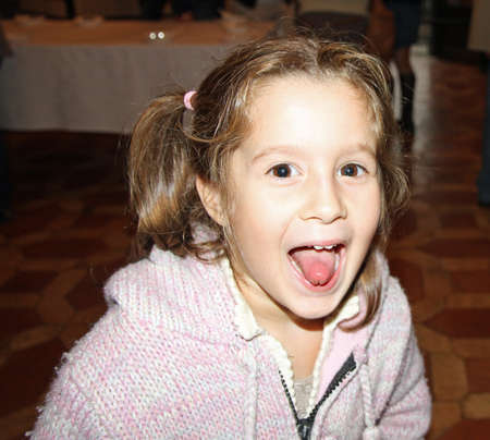 tongue out: young girls a bit monella pulls the tongue during a reception Stock Photo