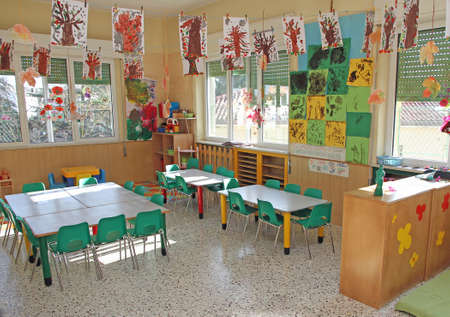 drawings of trees in autumn hanging from the ceiling in a class of kindergarten children