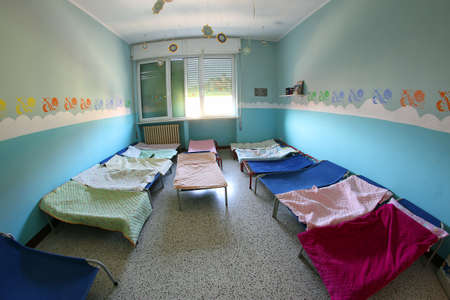 dormitory: small COTS with blankets for children in the kindergarten dormitory