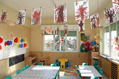 kindergarten classroom of children with many drawings of trees hanging from the ceiling Stock Photo