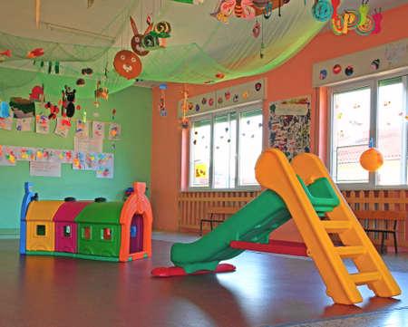 kindergarten toys: slide and plastic tunnel in the playroom kindergarten