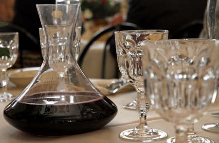 carafe decanter with red wine in a table with many glass of fine Bohemian glassware photo