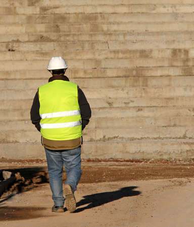 finite: Lone worker with the yellow high-visibility jacket as personal protective equipment and the large concrete staircase