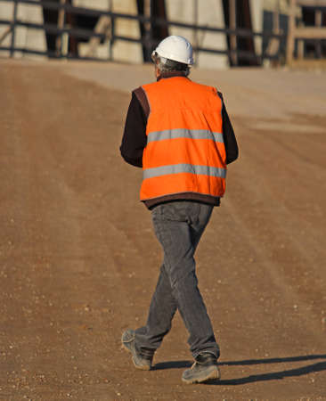 high visibility: worker with the Orange high visibility jacket as personal protective equipment within an immense construction site during construction of the building Stock Photo
