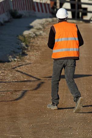 zichtbaarheid: werknemer met de Oranje hoge zichtbaarheid jas als persoonlijke beschermingsmiddelen in een bouwplaats tijdens de bouw van het gebouw Stockfoto