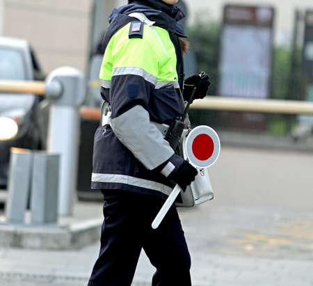 warden: Mujer polic�a con la paleta mientras dirigiendo el tr�fico en la ciudad