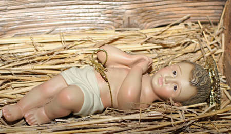 presepe: Baby Jesus is laid in the cradle in a manger with folded hands praying