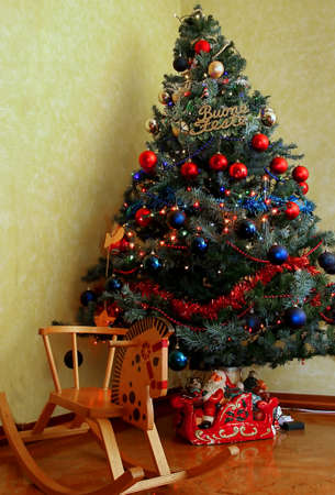 horse sleigh: large Christmas tree decorated to the nines with a wooden rocking horse and the Santas sleigh Stock Photo